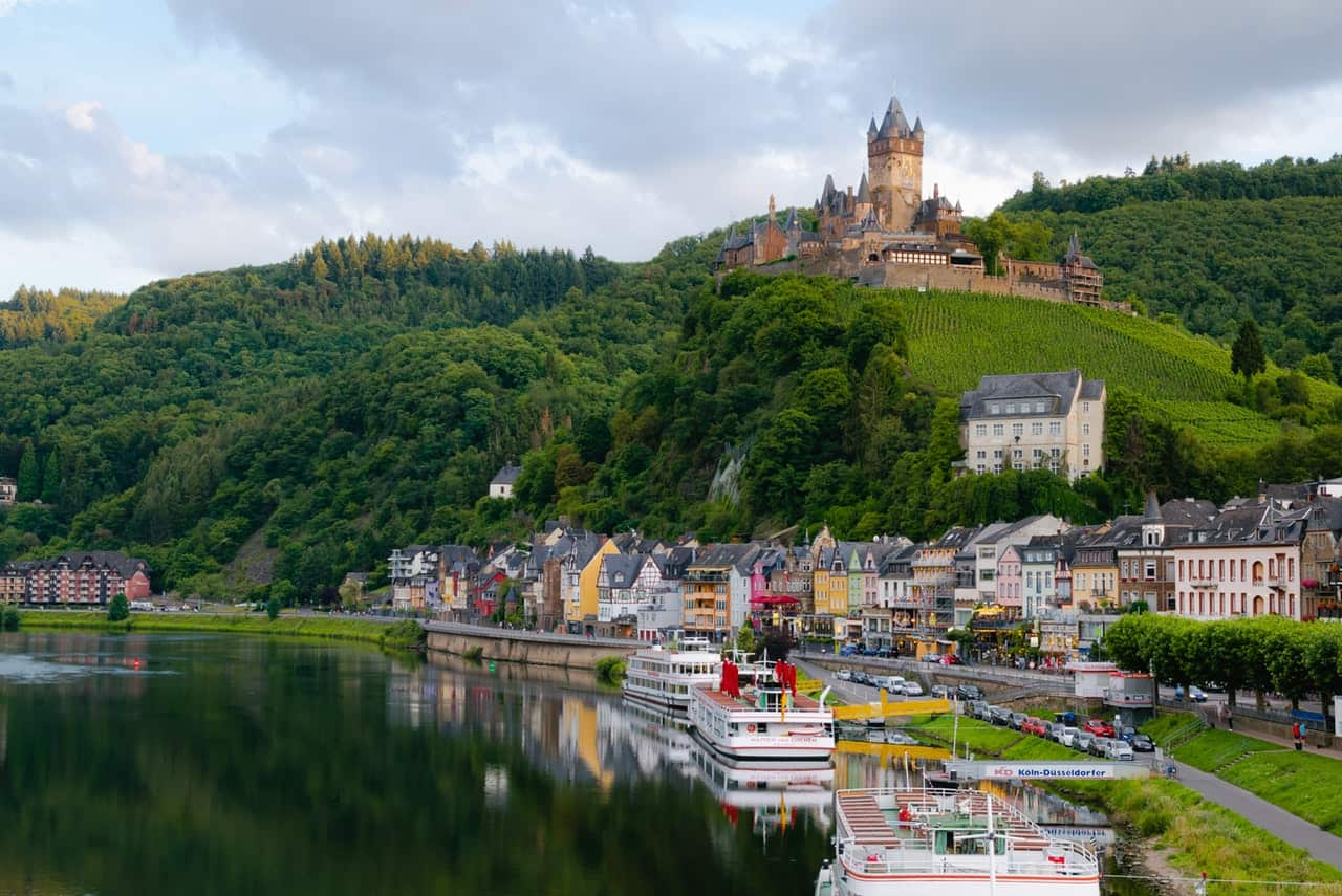 Boats on water and houses next to water with castle up on a hill
