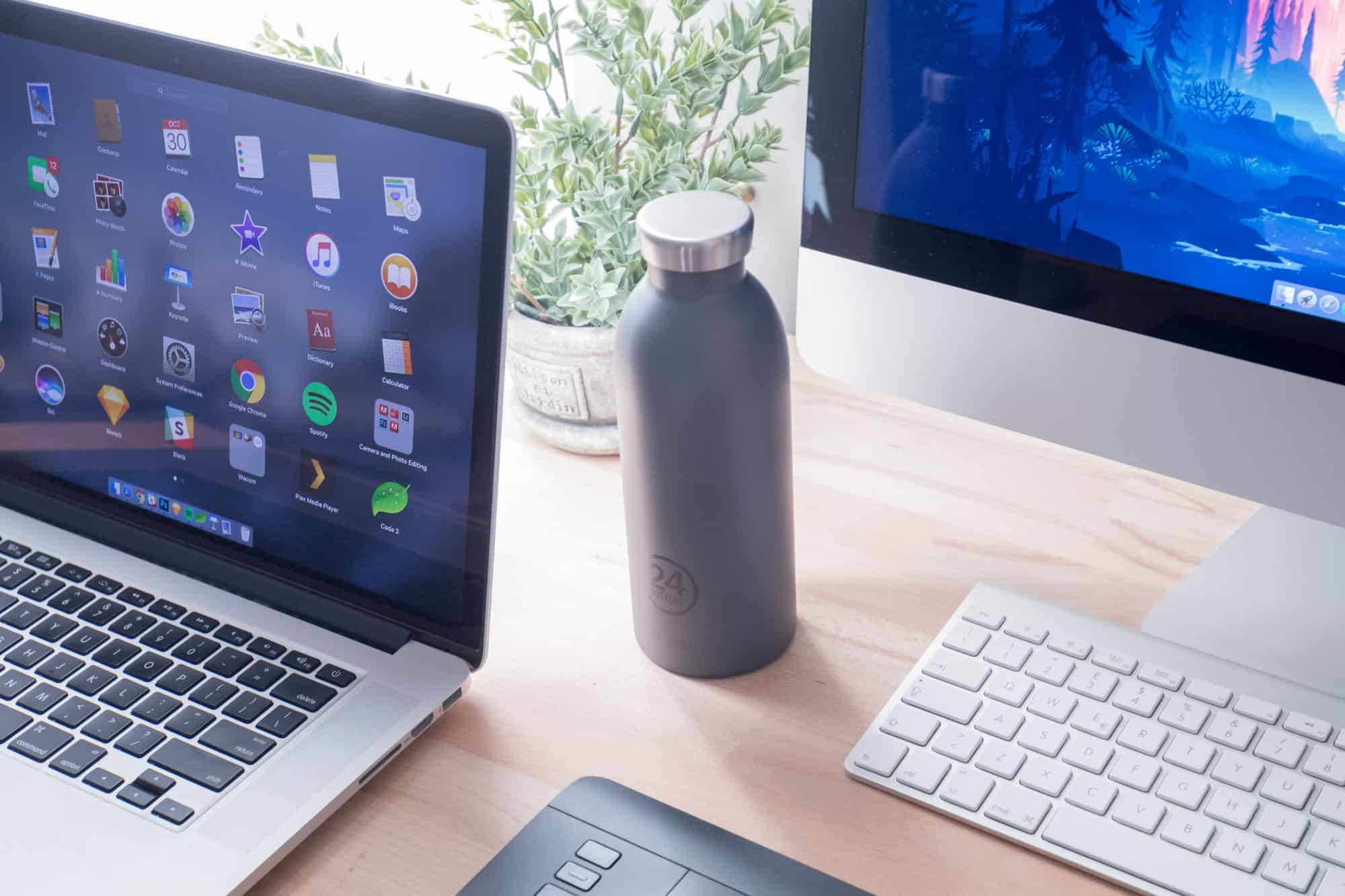 Water bottle on desk by laptop and desktop